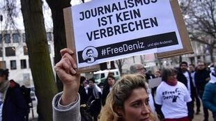 A woman holds a placard reading 'Journalism is not a crime' to protest the detention of German journalist Deniz Yucel in front of Turkish embassy in Berlin on February 28, 2017.