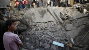 Palestinos miran una casa destruida por los bombardeos israelíes el domingo 18  de noviembre