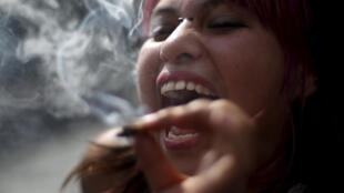 Une jeune Mexicaine, joint à la bouche, lors d'une manifestation pour la légalisation de la marijuana, devant le siège de la Cour suprême à Mexico, le 4 novembre 2015.