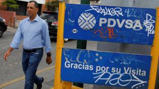 Un hombre camina frnete a un cartel de la empresa PDVSA en una gasolinera de Caracas, el 13 de noviembre de 2017.