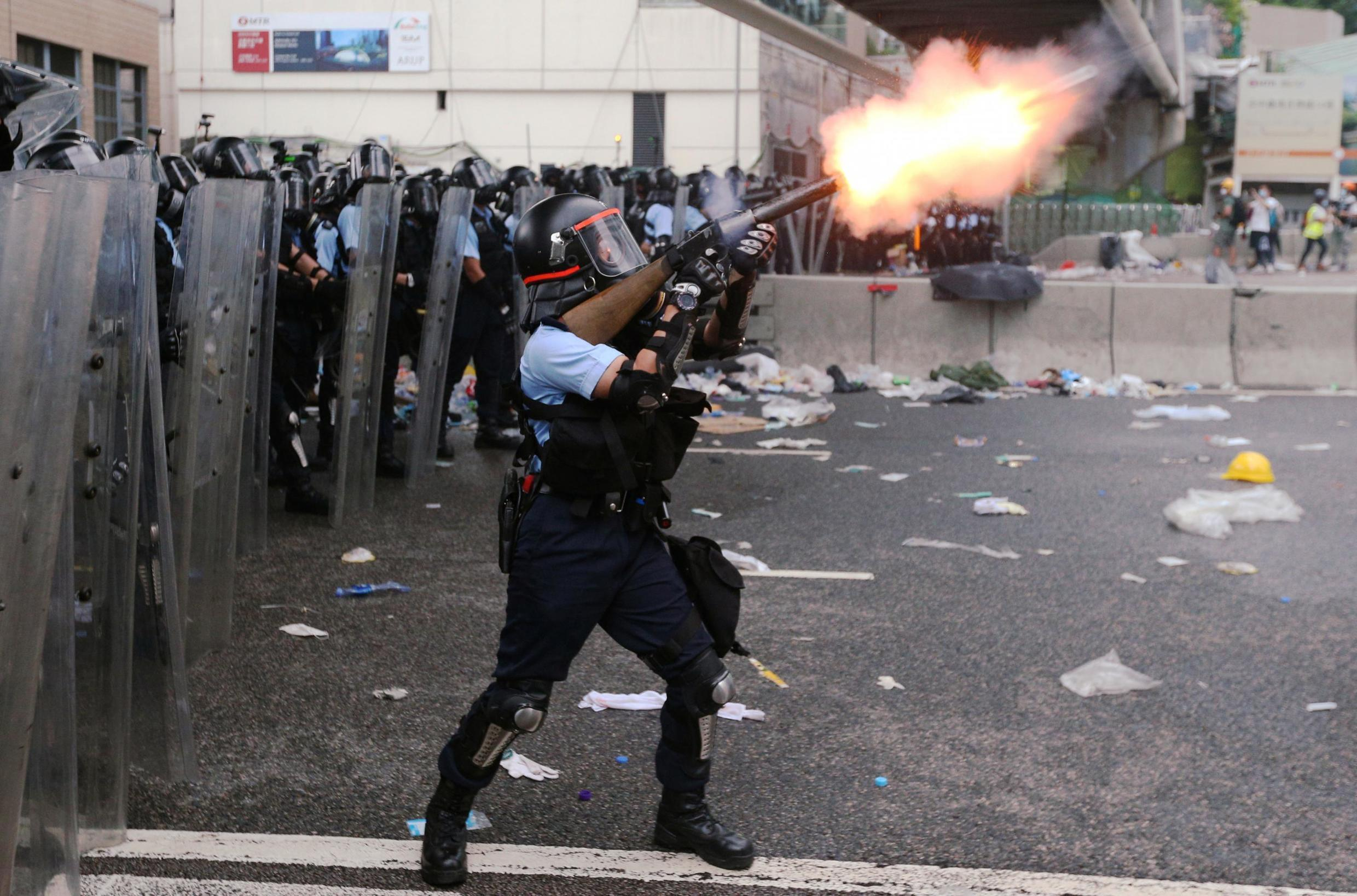 A police officer fires tear gas at protesters in Hong Kong on 12 June.