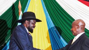 Salva Kiir (g) et le président ougandais Yoweri Museveni (d) lors de la signature de l'accord de paix, dont le retrait des troupes ougandaises est un point-clé.