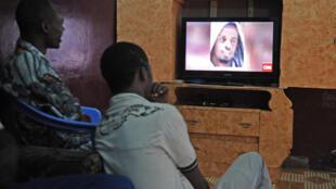 Somalis watch the news of Godane's death on CNN television