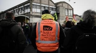 A SNCF unions member wearing an orange vest with slogans attends a meeting at the Gare de Lyon train station in Paris on January 29, 2020 over French government's plan to overhaul the country's retirement system