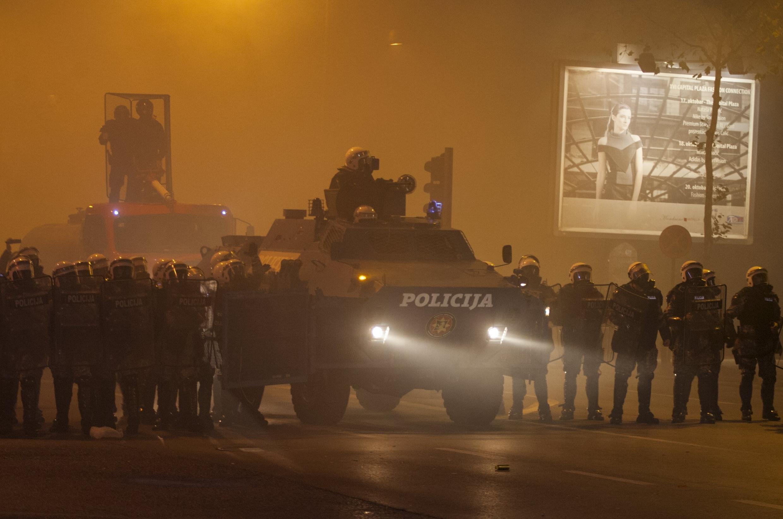 Des policiers anti-émeutes dans un nuage de gaz lacrymogène, devant le Parlement de Podgorica, le 24 octobre 2015.