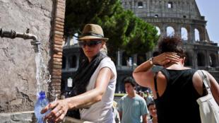 Des touristes remplissent leur bouteille d'eau dans une fontaine publique face au Colisée, à Rome.