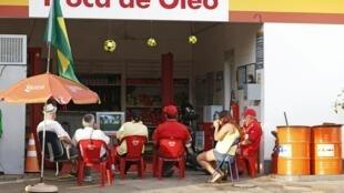 Funcionários de um posto de gasolina assistem pela televisão a um jogo da Copa, em Ribeirão Preto.