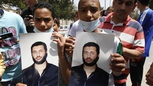 Deux jeunes manifestants exhibent le portrait de Saif Al-Arab Kadhjafi dans une rue de Tripoli.