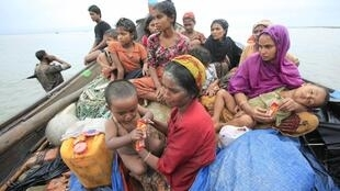 Rohingya refugees from Myanmar sit on a boat as they try to get into Bangladesh in Teknaf