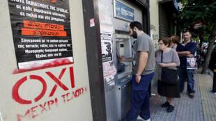 Cola frente a un cajero automático al lado de un afiche en favor del NO, Atenas, 3 de julio de 2015.