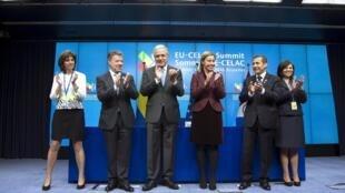 El presidente colombiano, Juan Manuel Santos, la jefa de la diplomacia europea, Federica Mogherini, el presidente de Perú, Ollanta Humala, y otros dignatarios europeos aplauden la firma del acuerdo que pone fin a las visas de turismo, 10 de junio de 2015.