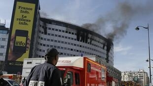 Smoke rises from the upper storeys of the Maison de la Radio in Paris