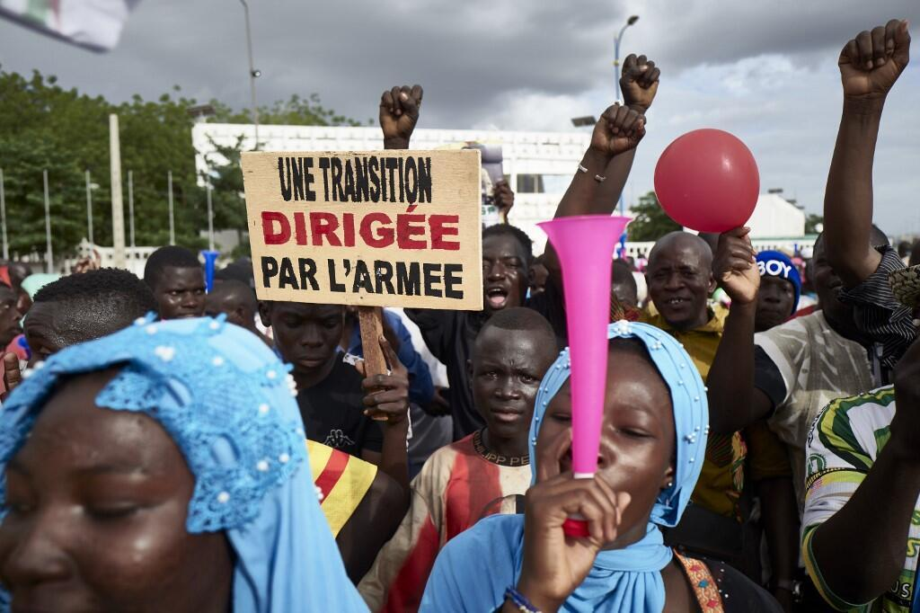 """A man holds a sign reading """"A transition led by the army"""" as supporters of the CNSP (National Committee for the Salvation of the People) take part in a rally on Independence square in Bamako,   on September 8, 2020"""