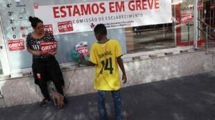 «Nous sommes en grêve», peut on lire à l'entrée d'une banque lors de la grève générale qui touche le Brésil, le 14 juin 2019 à Sao Paulo.