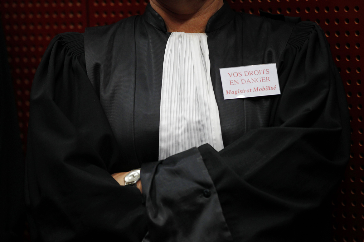 """A French magistrate wears a badge reading """"Your rights are in danger""""."""