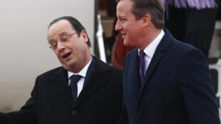 Britain's Prime Minister David Cameron (R) greets France's President Francois Hollande at RAF Brize Norton