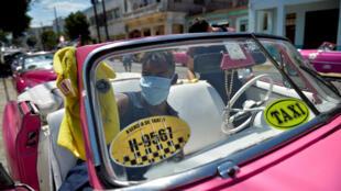 El conductor de un taxi privado limpia su automóvil en La Habana, el 19 de marzo de 2020