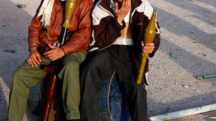 Rebels sit with rocket launchers at a checkpoint in Brega on Thursday.