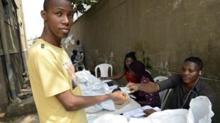 Un électeur nigérian se fait remettre une carte biométrique, contenant toutes ses informations, par un agent de la Céni, à Lagos, le 24 janvier 2015.