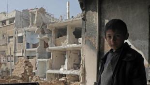 Un niño sirio frente a ruinas de edificios del reducto de Guta Oriental