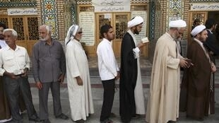 Men stand in line to vote at a mosque in Qom, 14 June, 2013
