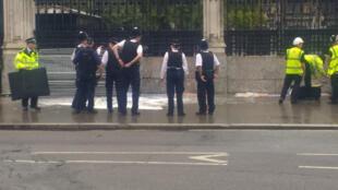 Policiais cercam o local, em frente Parlamento britânico, onde um homem se encharcou com gasolina nesta terça-feira (1°).