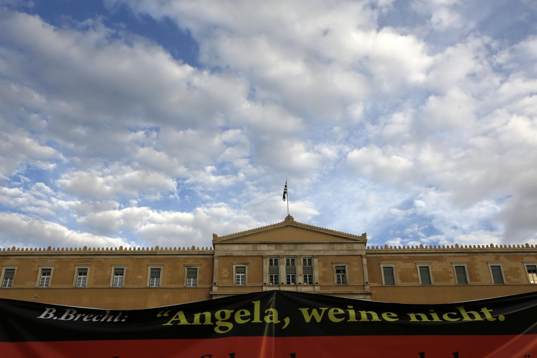 """Faixas de protesto com a frase """"Angela, não chore"""", foram colocas em frente ao parlamento grego  na véspera da visita da chanceler alemã a Atenas."""