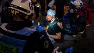 Médicos atienden al fotógrafo sirio Ameer al Halbi, que colabora con la agencia AFP, tras ser herido cuando cubría una manifestación por la libertad de prensa y contra la violencia policial el 28 de noviembre de 2020 en París