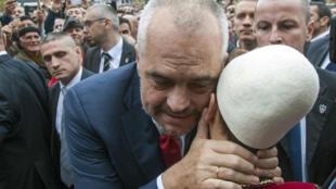 Edi Rama, Premier ministre albanais, ici avec un jeune portant un bonnet traditionnel albanais, lors d'une visite en 2014 à Presevo, ville de Serbie proche de la frontière avec le Kosovo.