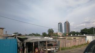 Brazzaville: au premier plan les maisons et échoppes du quartier Mpila, au second plan des immeubles en construction et au fond les deux tours jumelles, mars 2019.