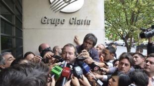 chefe da AFSCA, Martín Sabbatella, é cercado por jornalistas diante da sede do Clarín