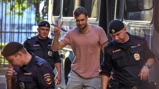 Pussy Riot punk group activist Pyotr Verzilov (C) with police outside a courthouse in Moscow earlier this year