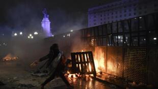 Une femme jette une bouteille aux agents de police anti-émeute devant le Congrès national à Buenos Aires, le 9 août 2018, après que les sénateurs ont rejeté le projet de loi visant à légaliser l'avortement.