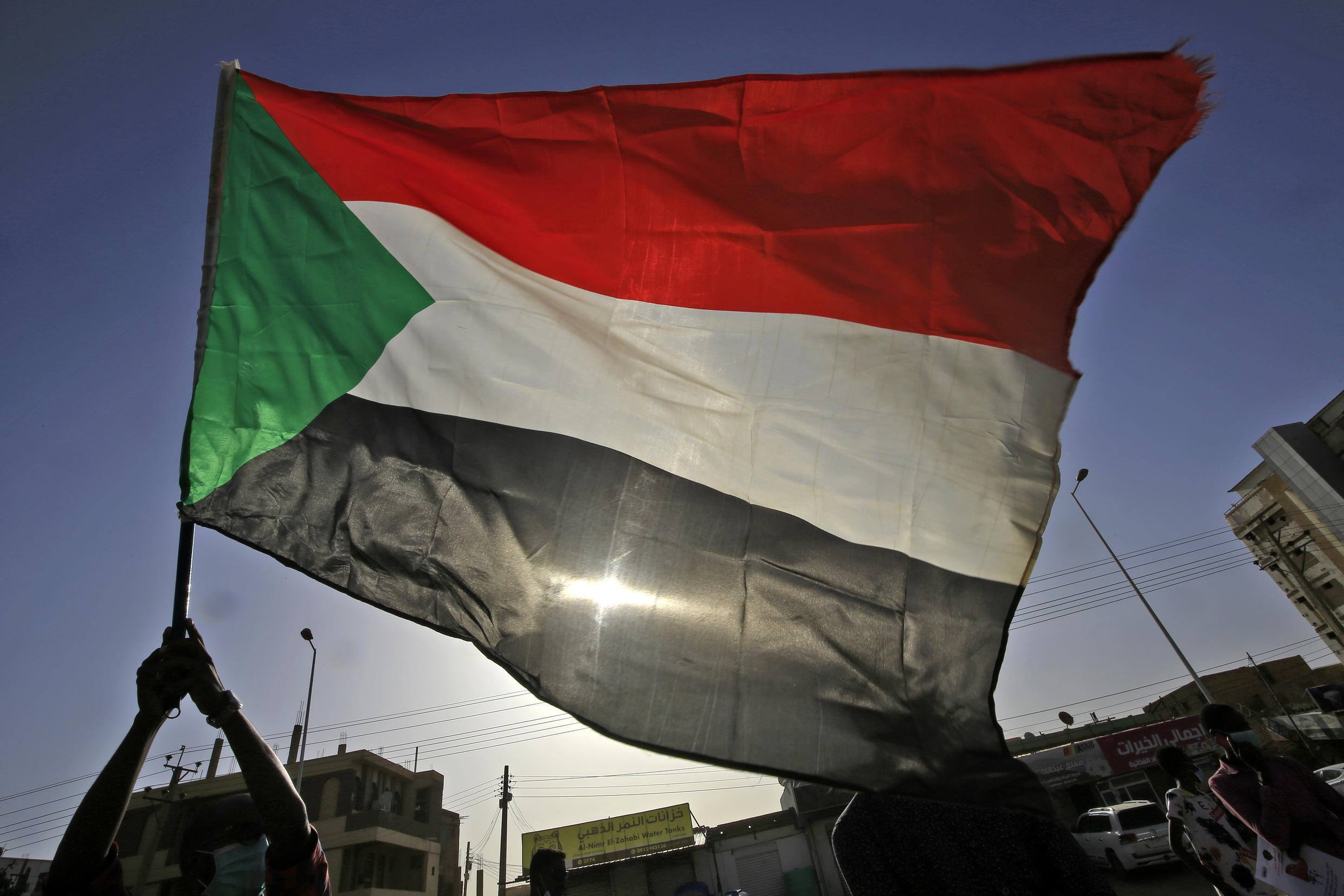 A Sudanese protester waves a national flag in the capital Khartoum in June 2020
