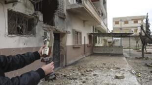 Sírio mostra restos de bombas e armamentos ao lado de residências destruídas nesta quarta-feira, em Homs.
