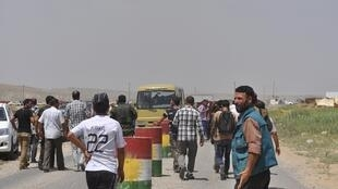 Displaced Yazidi families flee the violence as the walk on the outskirts of Sinjar, west of Mosul, on August 5, 2014.
