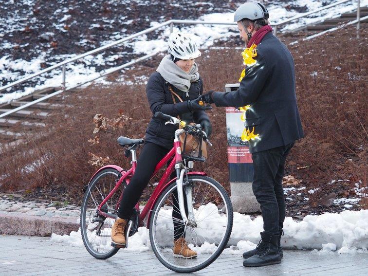 Un membre de l'association finlandaise Pyöräliitto distribue une lampe à une cycliste à Helsinki. Bien utile quand la nuit tombe à 15h30 l'hiver.