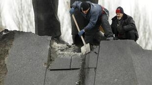 Workers clean debris on a monument that was partly damaged in an explosion in Donetsk.