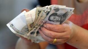 Chinesa manipula notas de Yuan em mercado de Pequim nesta quarta-feira, 12 de agosto de 2015.