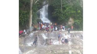 Des pèlerins sous la chute d'eau.