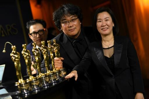 """(L-R) South Korean screenwriter Han Jin-won, director Bong Joon-ho and producer Kwak Sin-ae pose with their engraved Oscars for """"Parasite"""""""