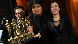 "(L-R) South Korean screenwriter Han Jin-won, director Bong Joon-ho and producer Kwak Sin-ae pose with their engraved Oscars for ""Parasite"""