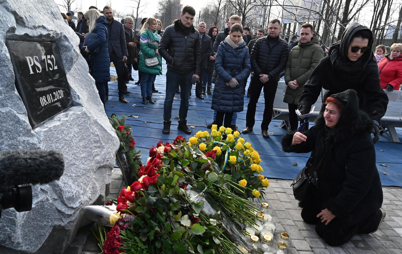 Les familles des victimes ukrainiennes de l'avion abattu par erreur par un missile iranien, se recueillent devant un mémorial érigé à l'aéroport de Bryspil, près de Kiev, le 17 février 2020.