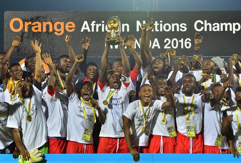 Le Congolais Joël Kimwaki soulève le trophée remis au vainqueur du Chan 2016, au milieu de ses partenaires.
