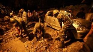 尼泊尔军人清理加德满都的英国大使馆附近因地震倒塌的围墙瓦砾(2011年9月18日晚间)