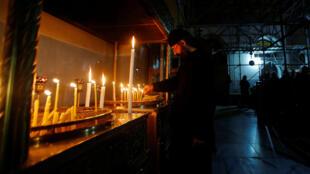 Un sacerdote limpia las velas colocadas en la Iglesia de la Natividad en Belén, Cisjordania, Territorios Palestinos, el 23 de diciembre de 2016.