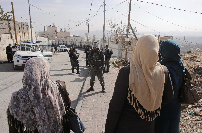 Des femmes palestiniennes face à des policiers israéliens dans le quartier de Jabal al-Mukaber à Jérusalem, le 18 novembre 2014.