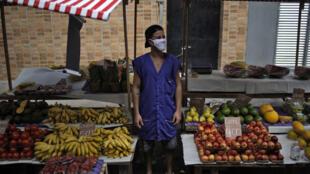 Un vendedor de frutas y verduras espera a los clientes después de la reapertura de los mercados callejeros en Rio de Janeiro, Brasil el 29 de abril de 2020, en medio de la pandemia de coronavirus