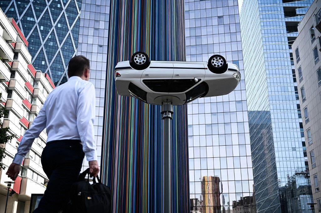 """2019年6月28日在巴黎西部拉德芳斯街区举行的当代艺术展览"""" Les Extatiques""""期间,一名男子走过了Benedetto Bufalino的一件题为""""路灯上的车""""的艺术装置。"""