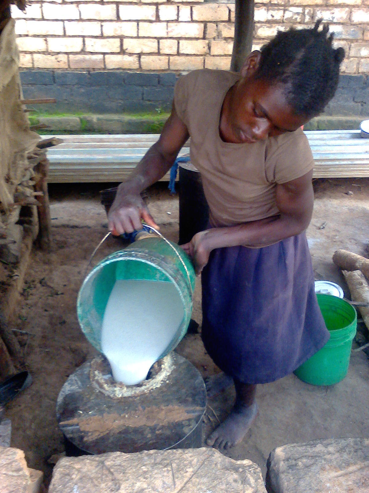 Girl brewing local beer in rural Zambia